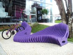 Clever stretched out slinky style bench bike rack also acts as sculptural focal point. For more great pics, follow www.bikeengines.com