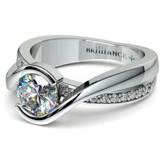 Exude elegance in the sleek beauty and diamond shimmer of the Bezel Diamond Bridge Engagement Ring in durable Platinum, featuring twenty round-cut diamonds in a pave setting accentuating the stunning center! www.brilliance.com