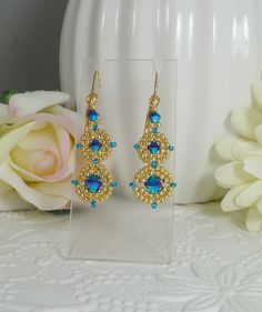 These hand woven earrings have two sizes of beautiful Swarovski crystals in blue ABx2. Woven in an a petite circular medallion design with tiny permanent finish golden seed beads and a touch of brilliant blue glass seed beads they make a gorgeous accent piece. The total length is 2 from the top of the lever back style ear wires. Design by Mandi Olaniyi. https://www.etsy.com/shop/IndulgedGirl