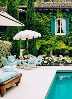 Outdoor patio umbrella and table with chairs. Patio furniture next to gorgeous pool and garden. Love the greenery attached to the house exterior. Parasols, Patio Umbrellas, Outdoor Rooms, Outdoor Living, Outdoor Decor, Teal Outdoor Furniture, Outdoor Chairs, Iron Furniture, Patio Chairs
