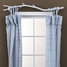 Tree branch curtain rod - Find a sturdy tree branch. Prune it and hang tied curtains on it. I think it would look best natural, rather than to paint it white as shown.
