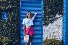 Awa Guimarães com blusa jeans e short rosa, ideal para dias de verão. A carteira divertida traz um charme a mais ao look.