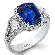 Passion Collection - This classically romantic 18K white gold ring showcases a stunning halo and .39ctw of round white diamonds, matching .55ctw emerald cut diamonds, and showcases a stunning 4.48ct natural blue sapphire. - TR540