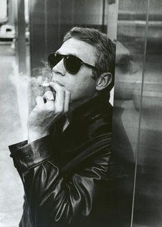 Steve McQueen in a black leather bomber jacket.
