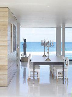 La elegancia de lo esencial. Rodeado de cristaleras, que enmarcan la línea del horizonte como una obra de arte, en este espacio, los muebles básicos componen un comedor de espectacular belleza. El grueso panel de madera blanqueada sirve de apoyo a una obra del propietario, Julian McGowan. La mesa es un prototipo de Gregor Jenkin. Las sillas de pino se esmaltaron en blanco salvo en sus extremos