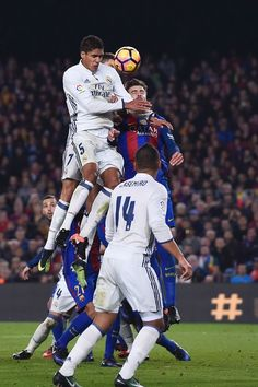 Real Madrid's French defender Raphael Varane (topL) heads the ball during the Spanish league football match FC Barcelona vs Real Madrid CF at the Camp Nou stadium in Barcelona on December 3, 2016. / AFP / JOSEP LAGO