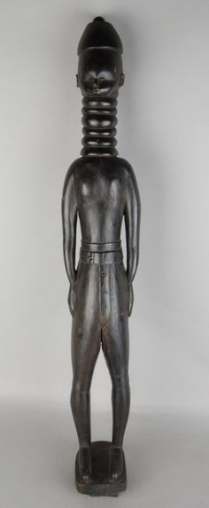 Full: Front Elongated black wood carving of a male figure wirh neck rings, elaborate coiffure and wearing European style short trousers. © The Trustees of the British Museum Neck Rings, Male Figure, Sierra Leone, British Museum, Black Wood, European Fashion, Wood Carving, Batman, Statue
