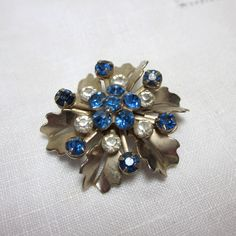 Blue Floral Brooch, Rhinestone and Gold tone pin with periwinkle crystals. Clear and blue rhinestones vintage flower brooch.. $8.00, via Etsy.