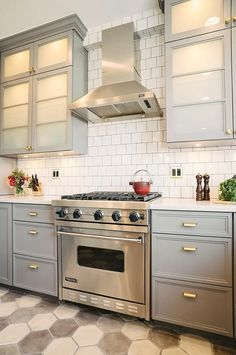 Fantastic gray kitchen features gray cabinets painted Benjamin Moore Cinder adorned with brass pulls, Schoolhouse Electric Card File Pulls in Natural Brass, topped with white quartz and a square white brick tiled backsplash alongside a white and gray hex concrete tiled floor.