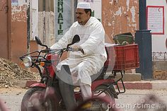 Muslim man on the motorbike, side dirty and destroyed street  citie Taroudant in Morocco