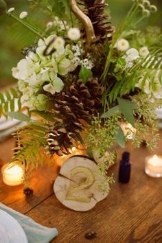 A woodsy wedding centerpiece with ferns and pine cone decorations.