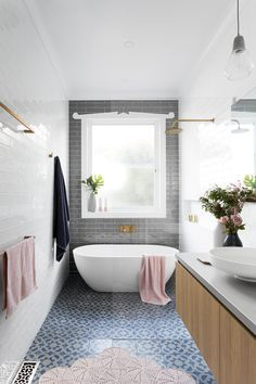Stunning bathroom! Gray subway tile from floor to ceiling. Blue floor tile and pink accents.