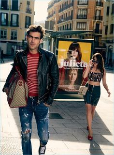 Jon Kortajarena wears a Dsquared2 jacket, belt, and denim jeans. Holding a Gucci bag, the Spanish model also wears a Sandro sweater and Converse sneakers.