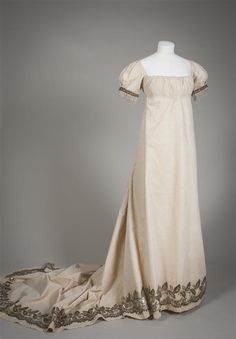Gala gown of cream silk with fine between tissue in narrow ridges of woven stripe motif , drag embroidered with silver thread beaten flat leaf motifs Identifier 0722347 Creation date 1800/1800 Silk Town msuem The Hague