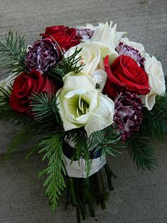 Winter wedding bouquet. Megan's bouquet featured deep red roses, dark purple carnations, ivory roses and amaryllis..finished off with winter greens.