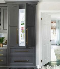 Beautiful concealed refrigerator behind grey cabinetry with gold hardware!