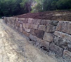 Reconstructed from its original stone and enhanced with granite blocks--this semi-dimensional wall makes a unique statement. Lake Landscaping, Landscaping Retaining Walls, Landscaping With Rocks, Small Natural Garden Ideas, Rock Retaining Wall, Stone Farms, Evergreen Landscape, Stone Wall Design, Building Stone