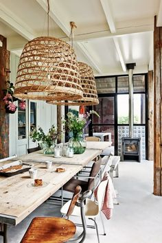 Rustic kitchen space with large wicker pendant lights, and a large farm-style table