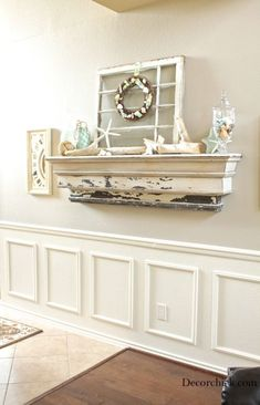 Creating a new summer mantel, shades of aqua, decorative balls, old antique window turned on its side, a simple shell wreath, the driftwood and the natural element it brings.