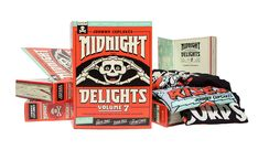Johnny Cupcakes have limited-edition shirts in a special package housed in a book. The theme of the product is 'Midnight Tonight'. The box is following the colour scheme of the t-shirts, it is an orange/ red background with white bold cartoon style text of Midnight Delights and a skeleton holding its head in between the text. The design fronts a comic style theme with the colours and text, the top of the box has a light blue strip. In the box there are pages to keep the book theme authentic