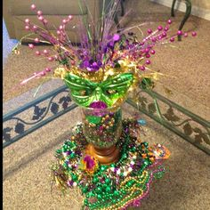 Don't know what do do with old Mardi Gras throws? Fill hurricane lamp and add coins and mask top with festive toppers and you have brand new Mardi gras home decor... And it didn't cost a dime!!