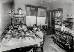 """Honest Household: August 1912. Roxbury, Mass. """"Home work on tags. Home of Martin Gibbons, 268 Centre Street. James 11, years old; Helen, 9 years; and Mary, 6, work on tags. Helen said she could tie the most (5,000 a day at 30 cents). Mary does some but can do only 1,000 a day. They work nights a good deal. The night before, Helen and James worked until 11 p.m."""" Photo by Lewis Wickes Hine."""