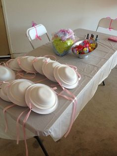 Tea party hat station - the 'hats' look like plates and bowls with ribbon. Smart! Add some flowers and boas and you're ready to roll.