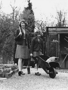 Princess Elizabeth (now Queen Elizabeth II, left) and her younger sister Princess Margaret Rose (1930-2002) in their garden at the Royal Lodge in Windsor Great Park, April 1940. The passenger in the wheelbarrow is a corgi named Carol.