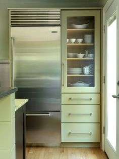 Opting for a narrow, shallow refrigerator netted more counter and shelf space in this compact kitchen. A tall cabinet with a mix of shelves and deep drawers maximizes storage space.