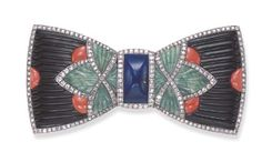 A RARE ART DECO HARDSTONE AND DIAMOND DEVANT DE CORSAGE, BY BOUCHERON -  Of mosaic design, the sculpted onyx ribbon bow, decorated with fluted jade foliate motifs and carved coral accents, to the central carved lapis lazuli knot, with circular and single-cut diamond trim, mounted in 18k white gold, circa 1925