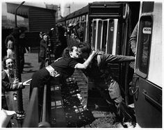 A woman leans over the railings at a railway station to kiss a soldier returning from the front of the Second World War.