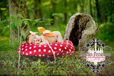 Newborn baby girl in orange butterfly wings on red mushroom.  Outdoor newborn session.  www.TheAthensNewbornPhotographer.com