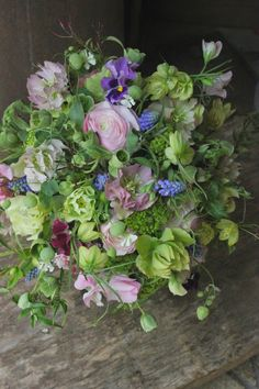 ranunculus, muscari, helleborus, lathyrus, alchemilla, viola. Lathyrus is not flowering at same time as the other flowers, maybe use early flowering clematis instead.