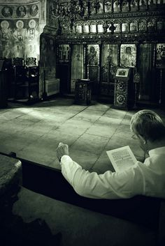 a German visitor reading the history of the place at Stavropoleos Monastery, Bucharest, Romania