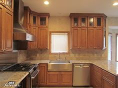 Stainless Steel Liances And Hood With Medium Brown Cabinets