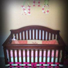 "Instead of using a traditional bed skirt get ribbon to make one!  Use Four rolls of 2"" ribbon and weave them in the crib bars like a basket."
