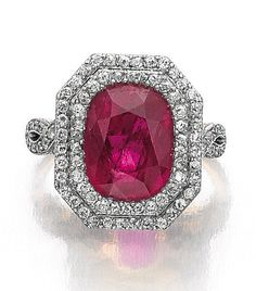 RUBY AND DIAMOND RING, CIRCA 1910. The cushion-shaped ruby framed within a double row of single-cut diamonds, the bifurcated shoulders similarly embellished