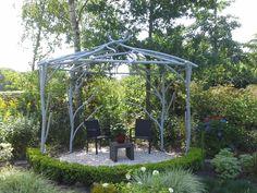 """Een prieel van metalen """"takken"""" is in deze kleurrijke en organisch belijnde tuin gerealiseerd.  Origineel, persoonlijk ensmaakvol.  Een mooie en beschutte zitplaats is hiermee gecreëerd. De """"takken"""" kunnenworden begroeid doorbijvoorbeeld klimrozen. Daarmeewordt deze blikvanger in de tuinzelfs nog bijna eenromantische theekoepel.  Een mooi en uniek project. Wederom maatwerk, zowel qua maatvoering als ontwerp.  Het geheel is in delen opgebouwd.  Tevens"""