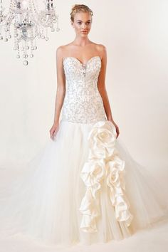 8386 Clarissa A dramatic gown with a detailed beaded dropped waist bodice, light tulle skirt, a floral piece
