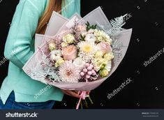 the girl is holding a beautiful bouquet in her hands