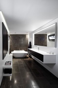 Modern lines master bath; continuation of floor material up bathtub wall. Light and dark contrast.