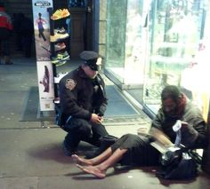 This Police Officer saw this homeless man had no shoes. He went and bought a new pair of shoes for the man.  He was unaware that the photographer was tracking this. My faith restored.