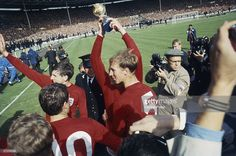 Martin Peters and Jack Charlton celebrate on the pitch after England's victory in the 1966 World Cup final at Wembley, July Captain Bobby Moore, obscured by Jack Charlton, holds the Jules Rimet trophy aloft. Jules Rimet Trophy, Retro Football, Football Team, 1966 World Cup Final, Martin Peters, Jack Charlton, Bobby Moore, England Football, Historical Photos
