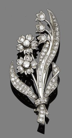 A diamond spray brooch, circa 1910.  The floral spray set throughout with brilliant, single and baguette-cut diamonds, diamonds approx. 1.45cts total, length 6.2cm, fitted case
