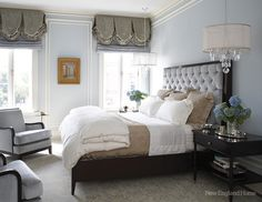 Love the double chandeliers in this master bedroom.  Very elegant and romantic.  The tufted bed is exquisite. The walls of pale sky-blue trimmed in white add to the serenity.
