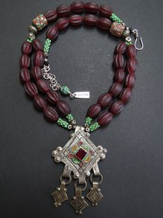 by Luda Hunter | Double strand ethnic necklace of maroon Nepalese melon glass beads, antique green African flower trade beads and 2 antique African eye glass trade beads from the late 1800's. The enamel niello pendant with red glass cabachon and 3 dangles is from Tiznit Morocco. Lots of antique cornerless silver Tuareg beads, Ethiopian silver beads and a 9.25 sterling silver extension chain and clasp. | 337.31 $