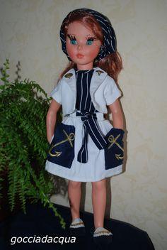 Sheila con un completo alla marinara in pquè bianco: ampia gonna con le ancore ricamate in oro sui tasconi blu e corto bolerino coi bottoni marina. Mocassini bicolori