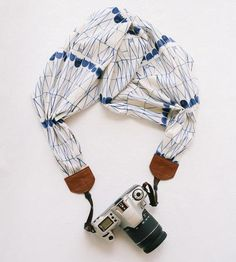 An all-in-one strap and adornment, this scarf camera strap turns your equipment into a new accessory. Made of sturdy cotton fabric secured by heavy-duty leather tabs, the strap patterns an abstract geometric of indigo tulips on an ivory field. Just thread the nylon strapping through the loops on your DSLR to wear it to your next session.