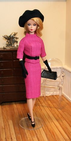 This two piece daytime suit is styled in pink textured weave.  The top and skirt are fully lined; the top has a funnel neckline and closes at the back with snaps under button trim. The skirt is below knee length and closes with a snap.  The accessories are in black; the belt has a front knot and closes with a hook and loop, the knit beret is oversized; the clutch bag is real leather and the gloves are day length. Model Betty Draper Silkstone Barbie and shoes not included. Shipping to the…