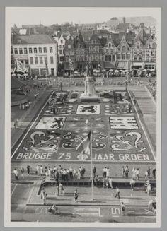 Bloementapijt op de Markt, opname vanuit het Belfort.Naar aanleiding van het 75-jarig bestaan van de Groendienst werd op de Markt een reusachtig bloementapijt aangelegd. Bemerk de drie wapenschilden, van links naar rechts, het           wapenschild van West-Vlaanderen, dat van Vlaanderen en dat van de stad Brugge. In het midden het standbeeld van Jan Breydel en Pieter de Coninc. Bemerk links de gevelopschriften van           Tea-room Theissen en CODEP Spaarkas/PS Verzekeringen.Brugge…